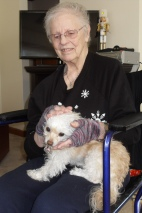 Patricia Shaner wears the gloves given to her by Red Cross volunteer Bonnie Brown while holding the family dog Dilly.
